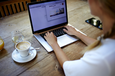 Open laptop and cup of coffee on wooden table; women's hands typing on laptop.