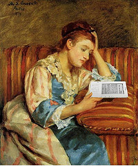 old-fashioned-looking lady seated on antique couch reading from a tablet