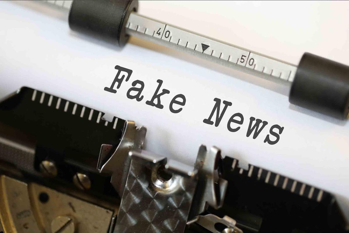 "The image shows a typewritten headline on white paper ""Fake News'."