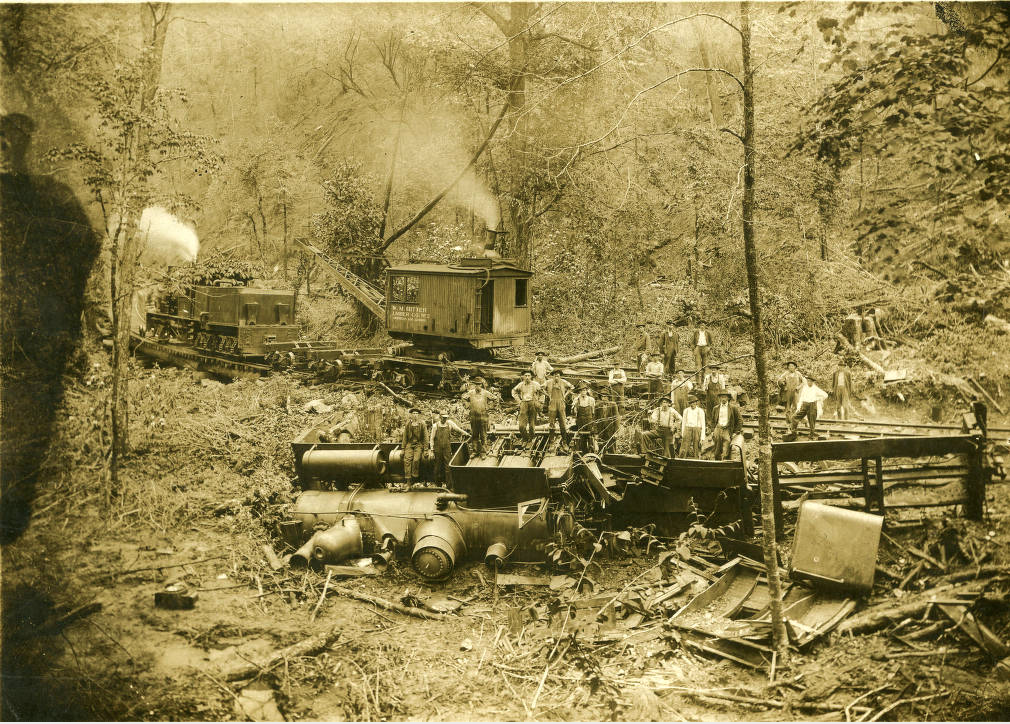 "Engineer Frank Bailey, Brakeman Ervin Nichols, carrying 12 carloads of logs.(Also described as ""Hazel Creek Train Wreck""). Locomotive shown on its side following wreck. Date, 1916. Brakeman Nichols failed to perform duty and caused wreck."