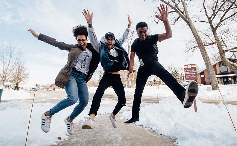 Photo of three students jumping in the air
