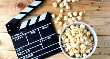 Photo of a film clapboard and popcorn