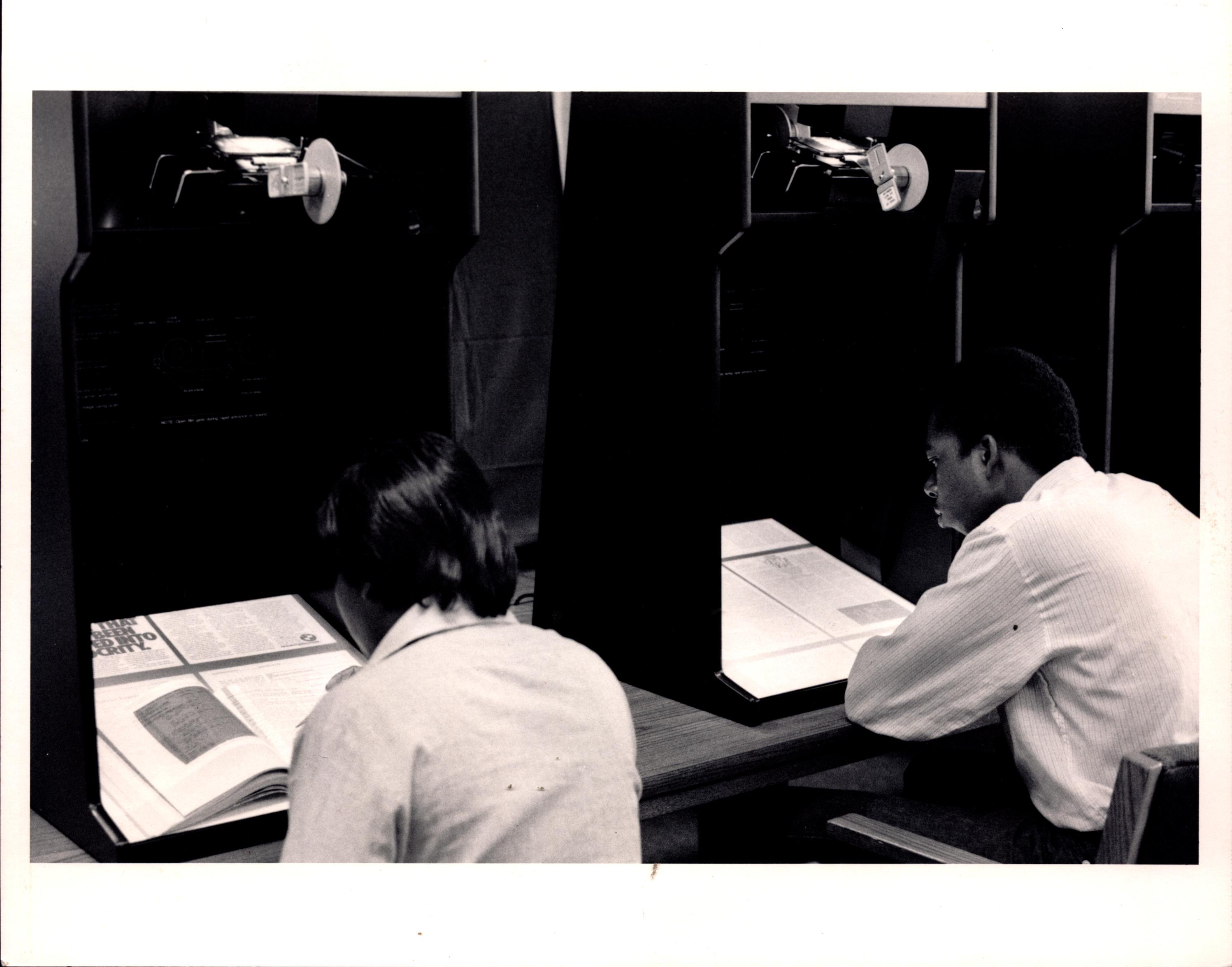 Students using microfilm reader.