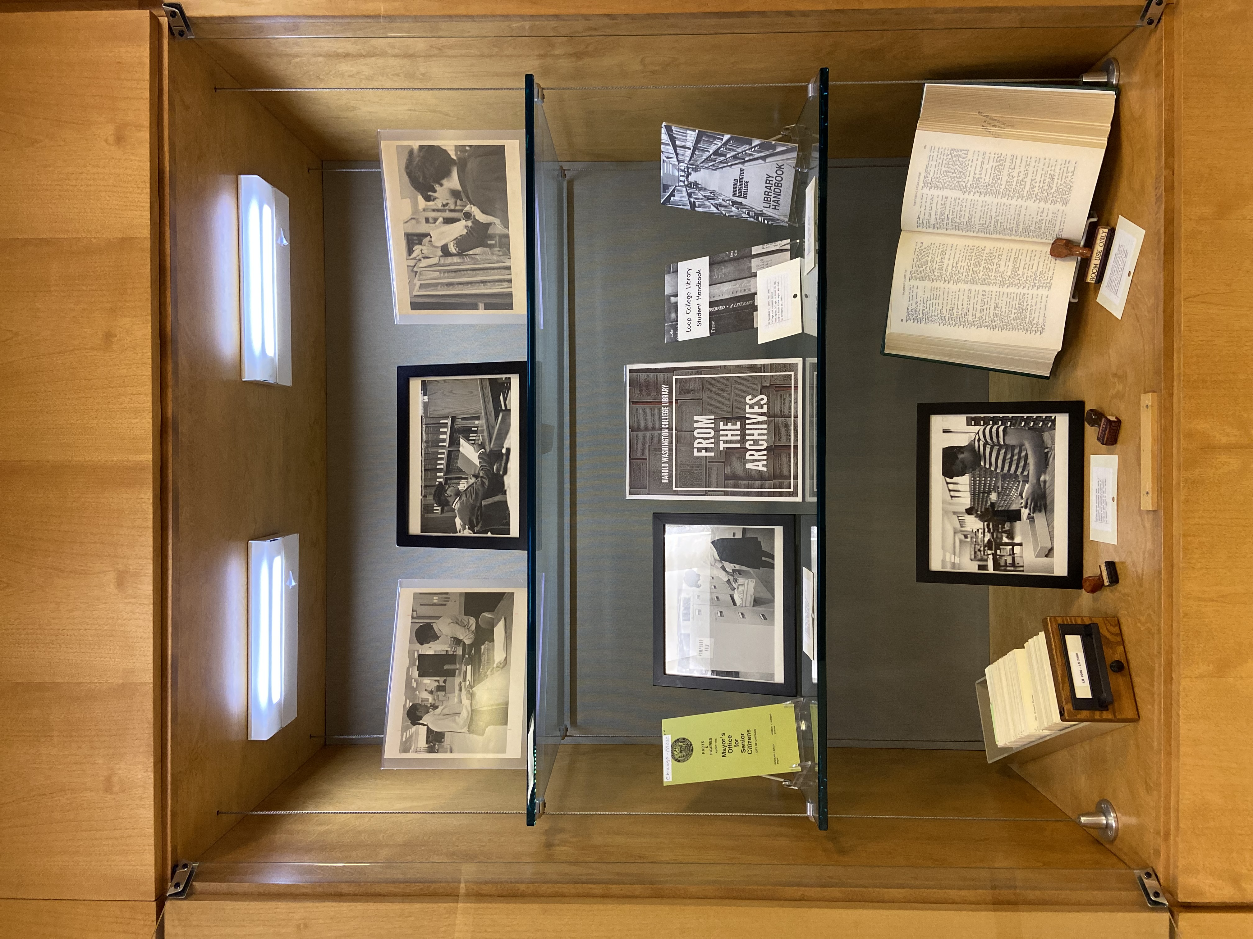 Photo of display case with obsolete library items and photographs of the library from the 1980s.