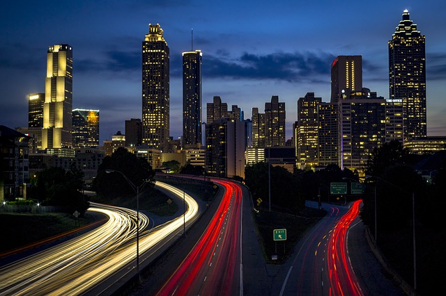 Night time view of a major city skyline with highways in the foreground