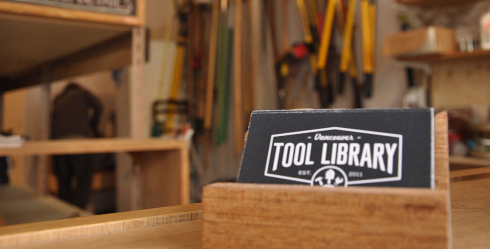 Tool library sign in a room full of tools