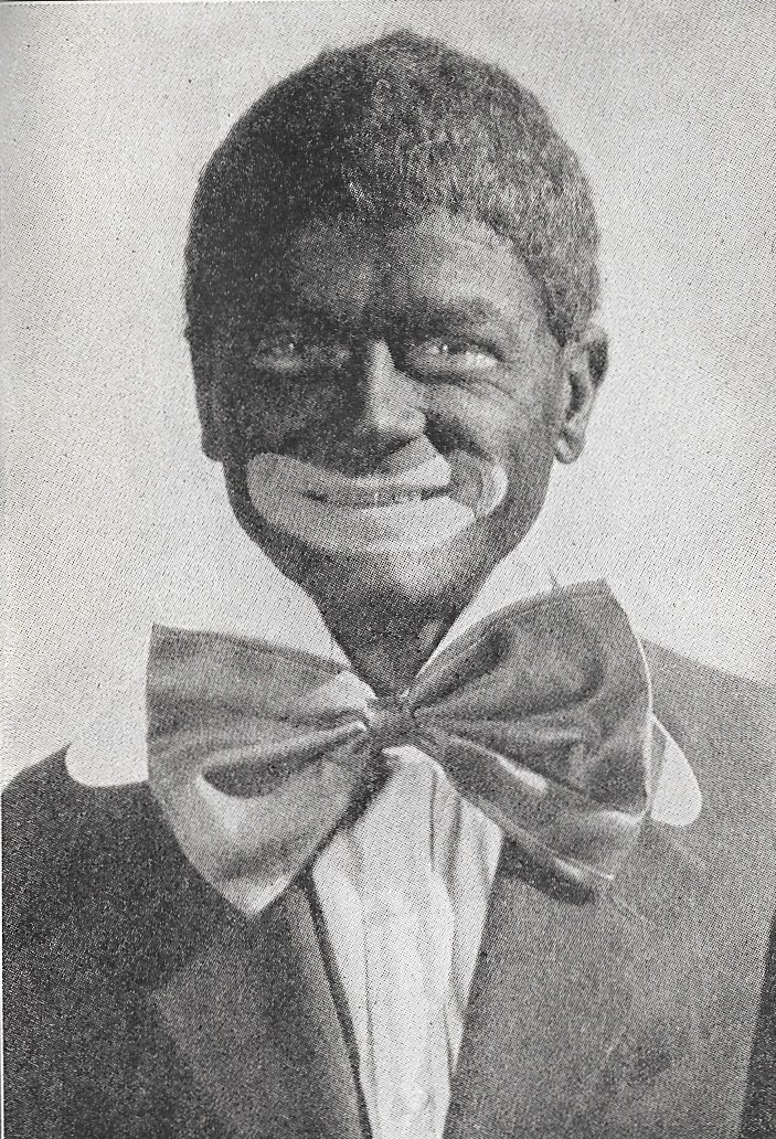 White actor in full blackface makeup, hair, and costume.