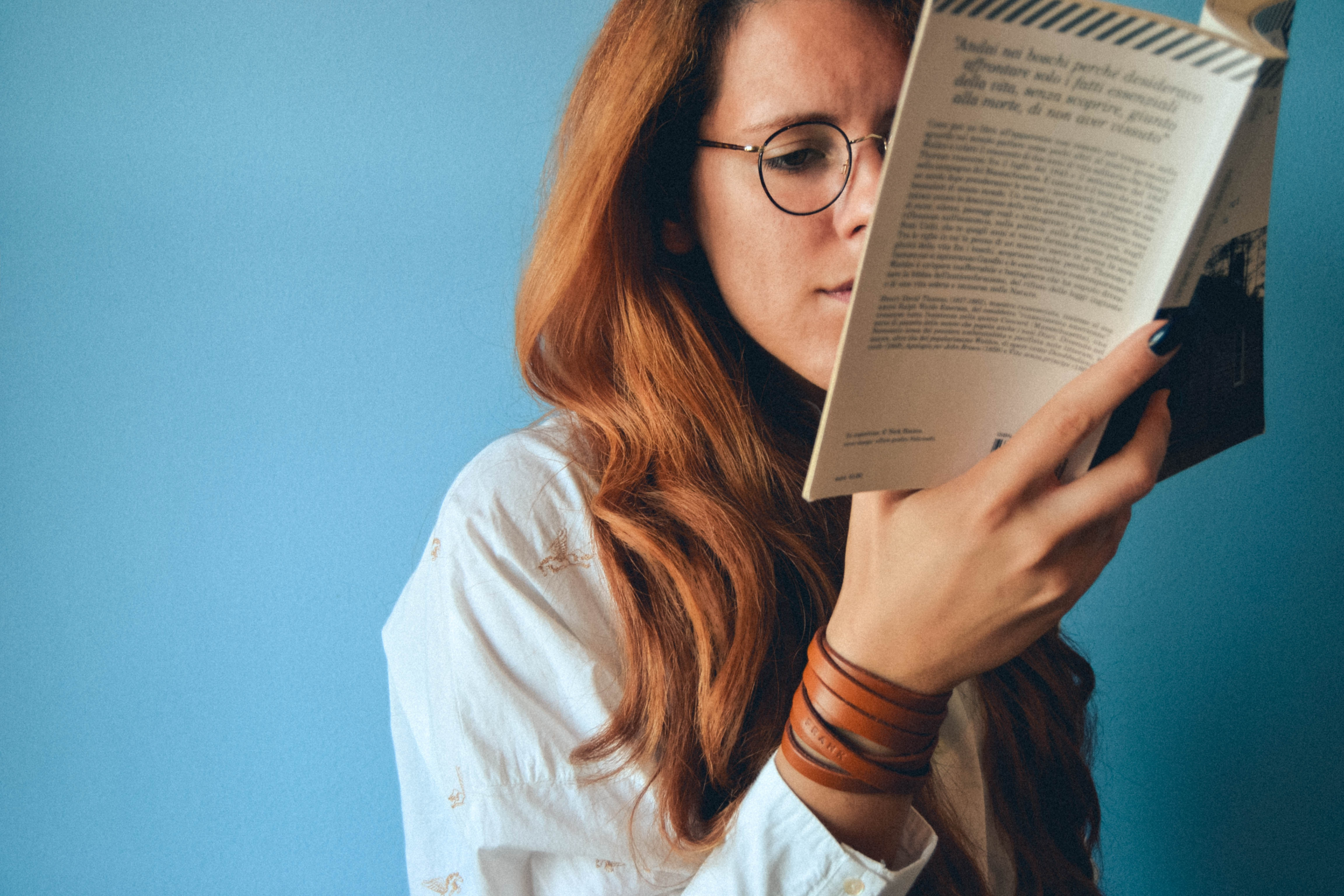 woman looking closely at book