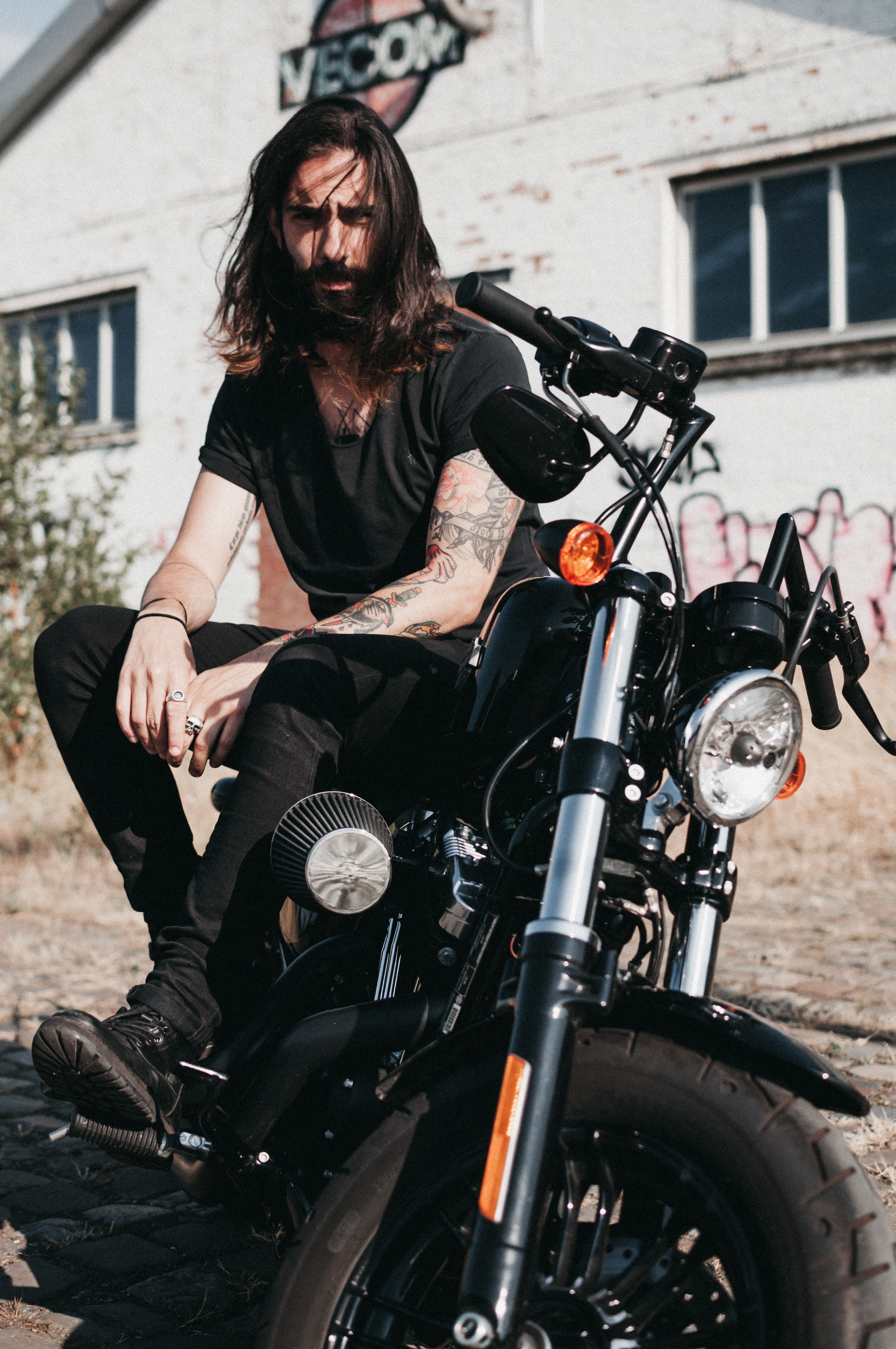 Man with long hair sitting on a motorcycle in Belgium.
