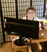 smiling woman sitting at computer in home office