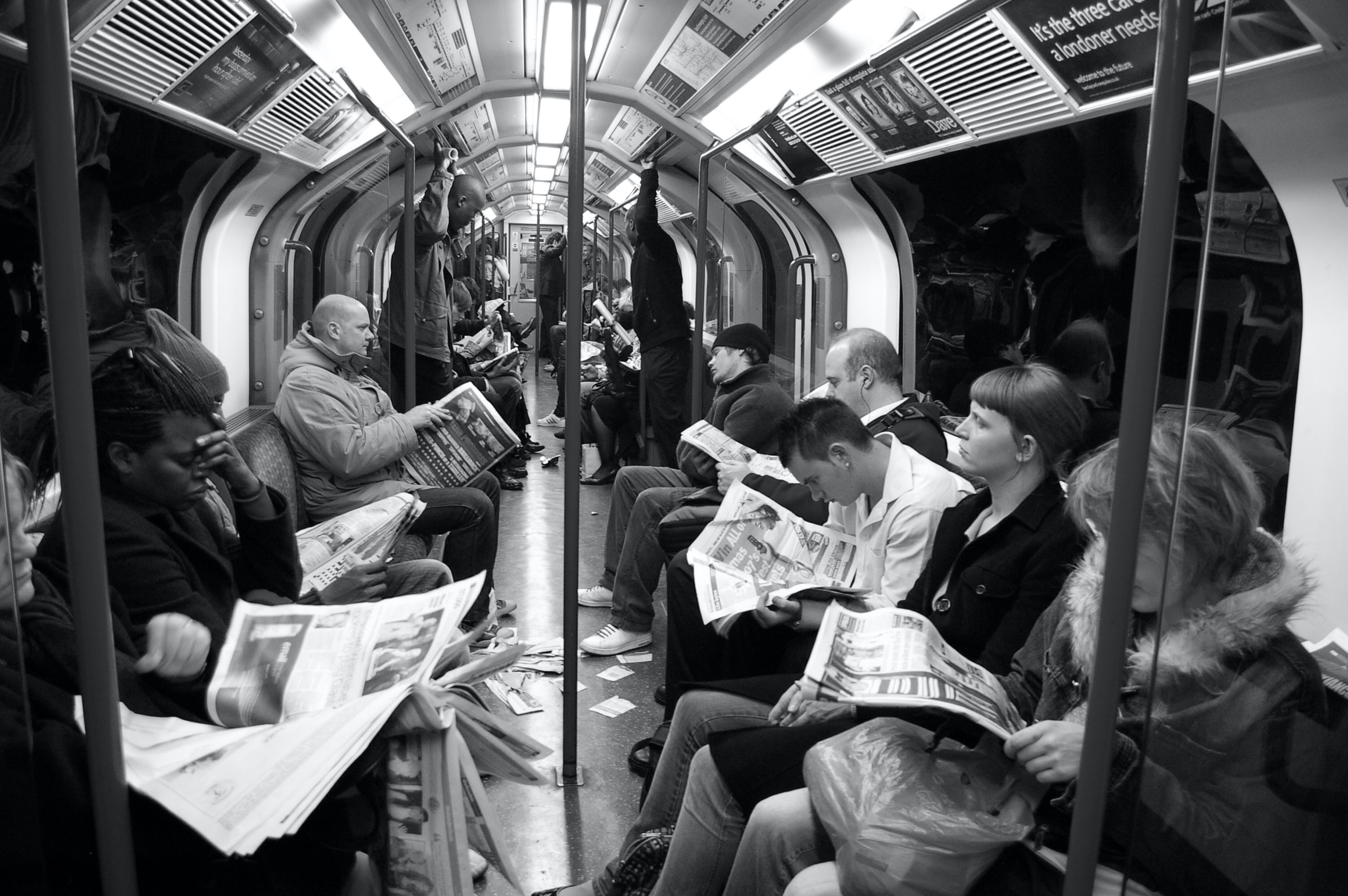 black & white photo of people reading newspapers on a train