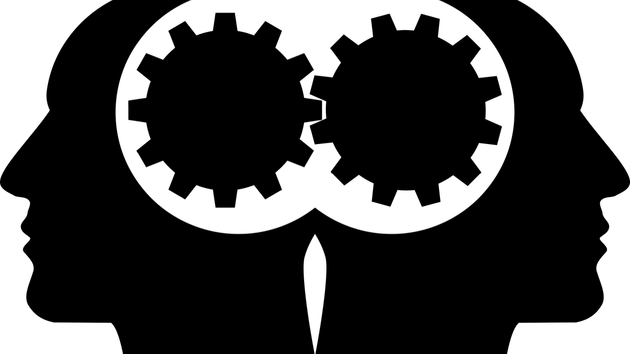 two black head silhouettes with intertwined gears connecting