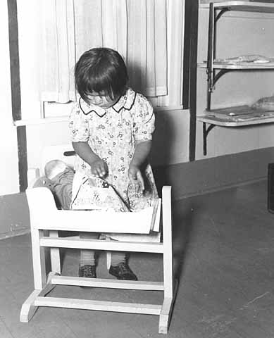 Girl with doll in crib, nursery school at Nett Lake