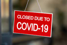 sign that says closed due to covid-19
