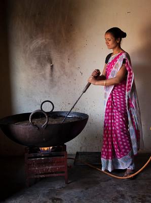 woman making medicine in iron kettle