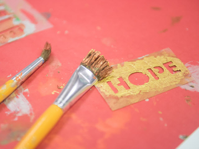 Image of art supplies and a stencil with the word hope