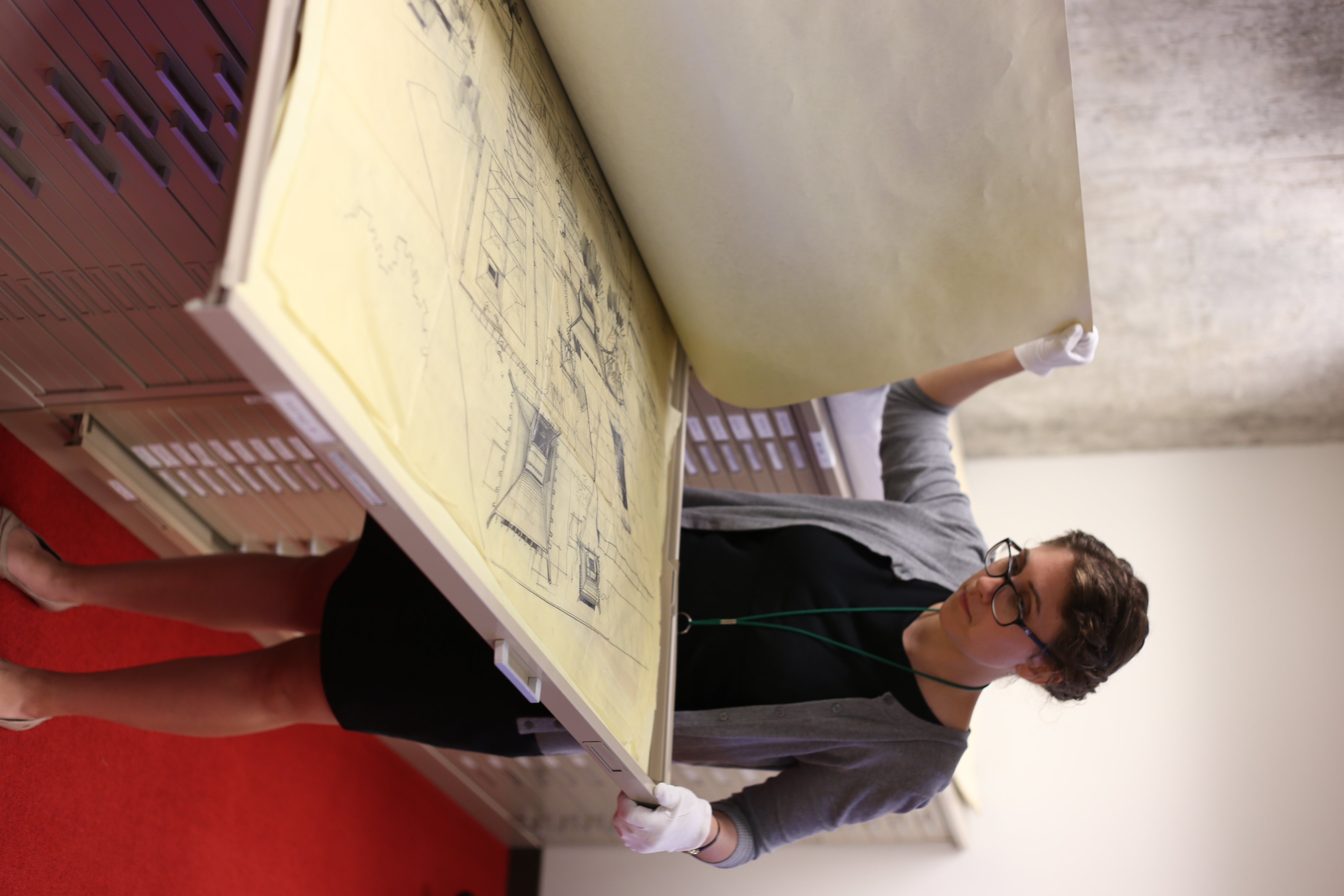Staff person is opening a large folder that holds architectural drawings on tissue.