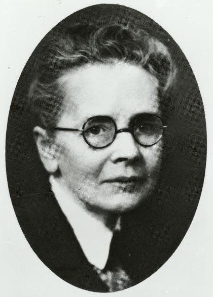 Oval black and white portrait of Julia Morgan wearing glasses