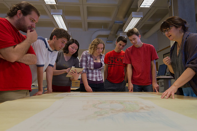 Students and archives staff person examining an architectural drawing on a table in the archives