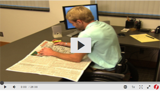 Screenshot of a streaming video, showing a man in a wheelchair at a desk, reading a paper with a highlighter in his hand