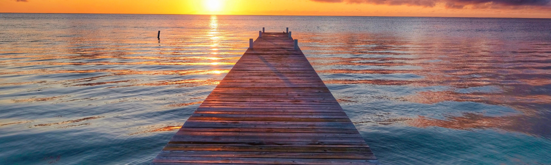 A bridge, stretching out into calm waters during sunset.