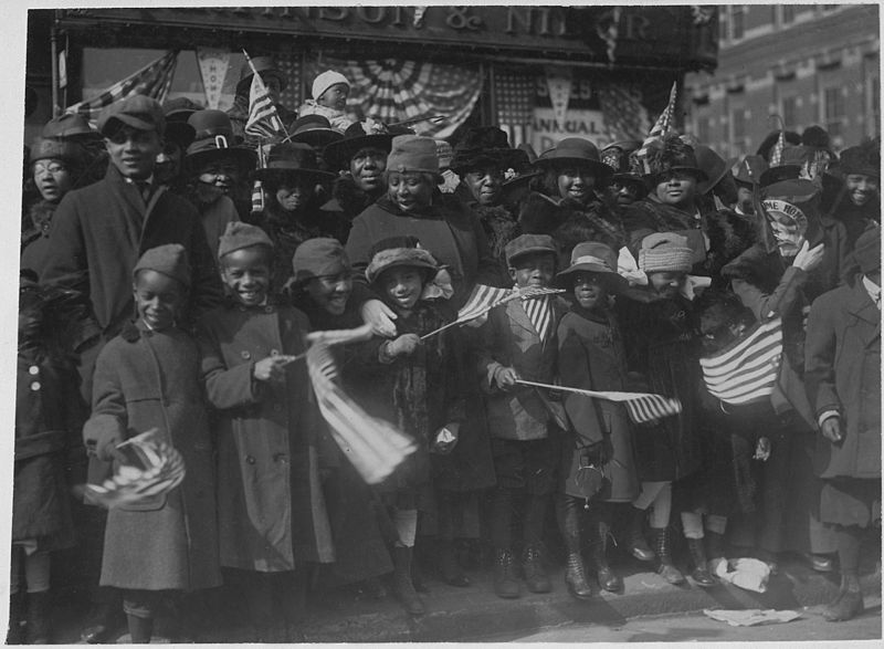 Crowd of African American men, women, and children holding and waving American flags, ca. 1919
