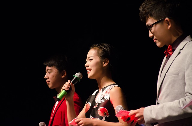 Young Asian American woman in a stage holding a microphone, with a young man on either side of her