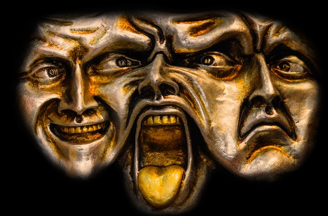 Intersecting bronze faces which show happy, angry, and sad expressions