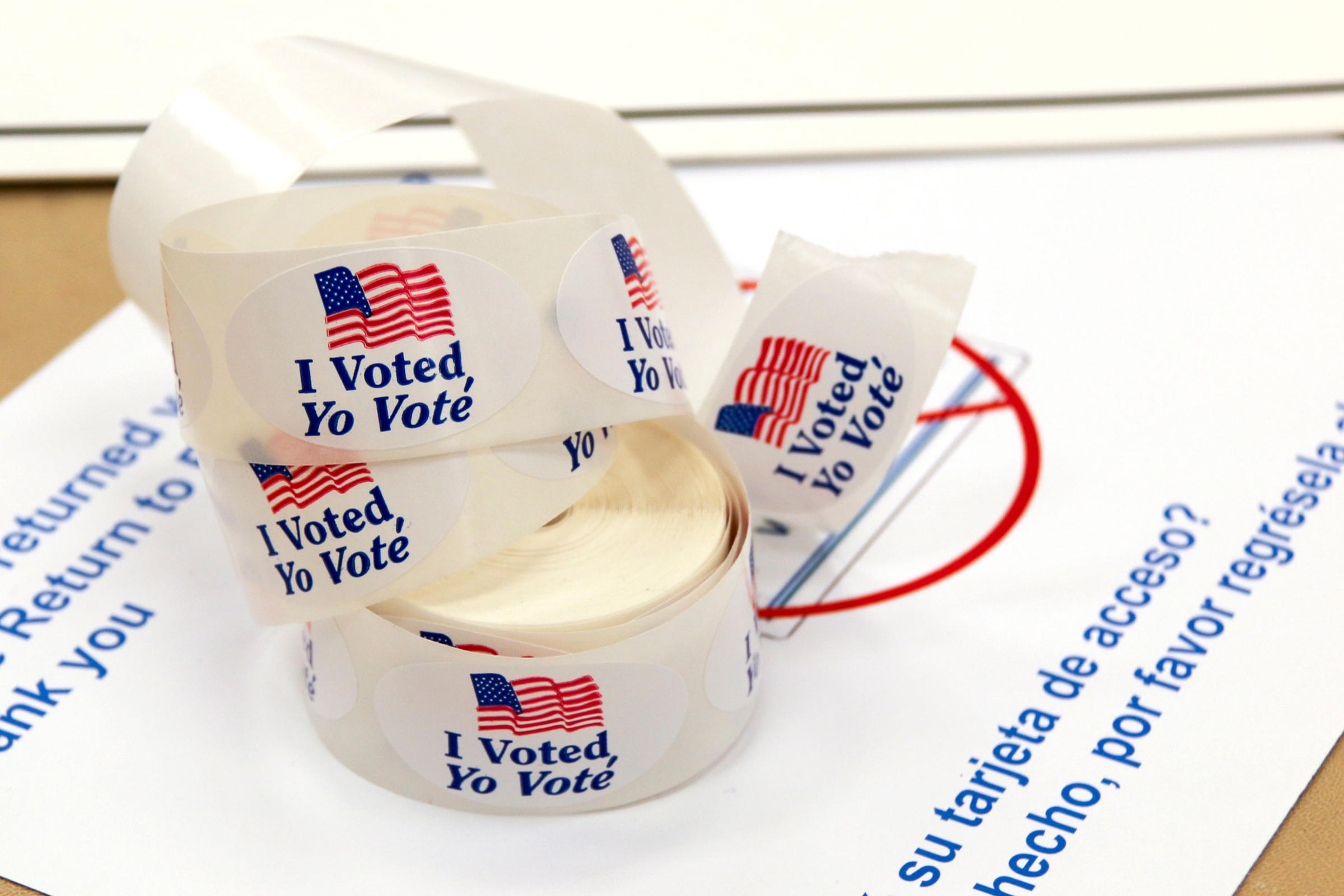 """Roll of ovular shaped white stickers with an american flag and the text, """"I Voted, Yo Voté."""""""