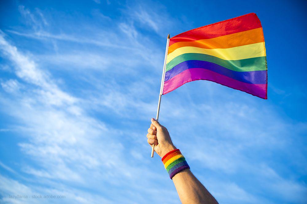 hand holding a rainbow flag