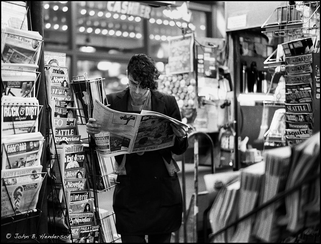 Man reading in a Seattle newsstand