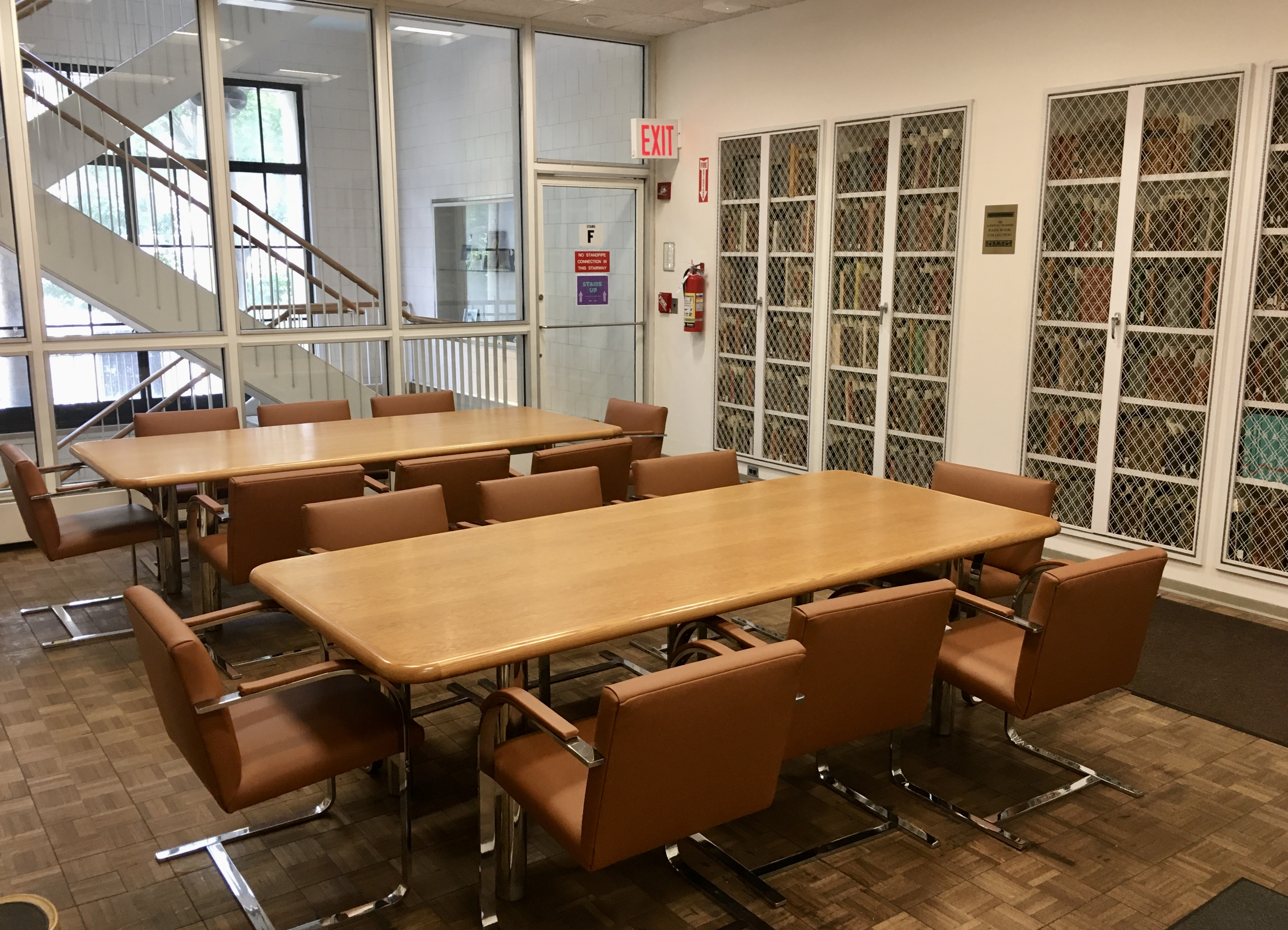 Tables, chairs and bookshelves in the Reading Room of the Conservation Center Library.