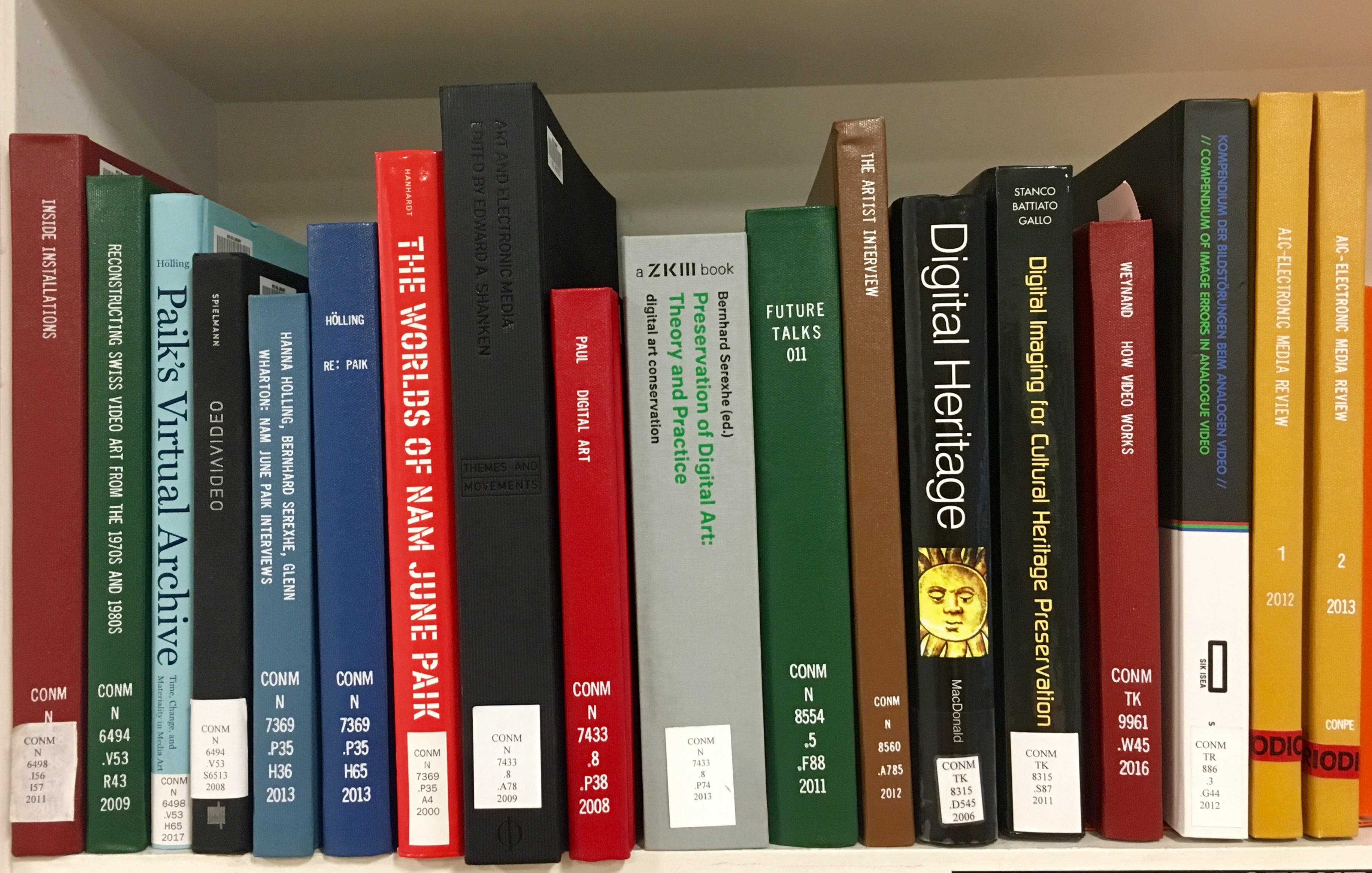 A bookshelf showing the spines of new books on time-based media.