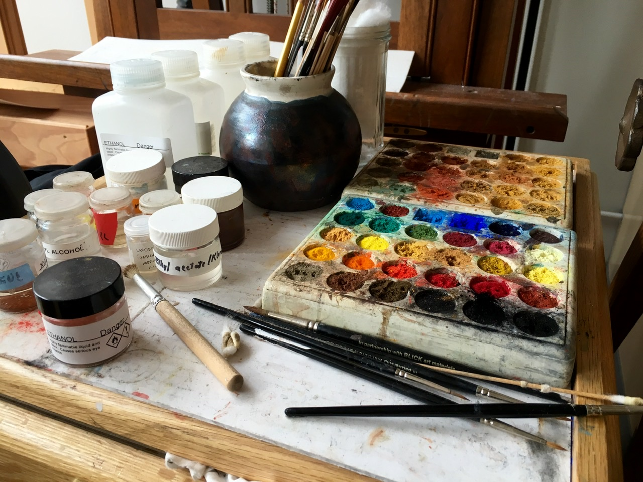 A painting conservator's worktable with palette and brush.