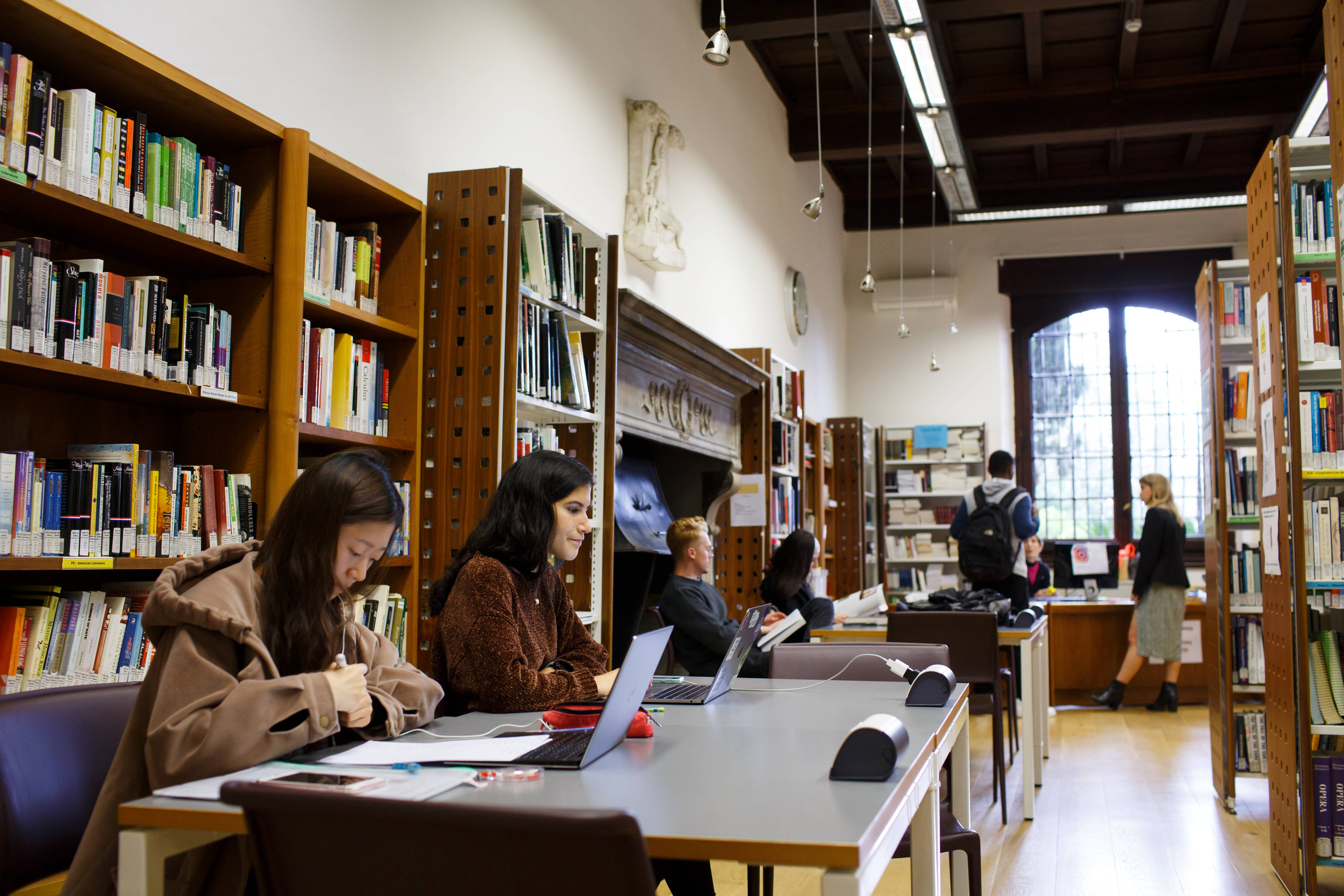 Students seated at desks in the library, reading books and working on their computer.