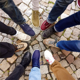 a group of students putting their feet in a circle - to compare shoes