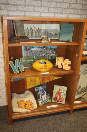 Top Shelf --      Arthur Best, class of 1900, textbooks     PMC Saber Letter Opener     Cadet Belt and Buckle     Cadet Regulation Book, 1954  Middle Shelf --      1959 PMC Football     PMC and Widener Patches  Bottom Shelf --      Athletic Sweater, MAC Football Championship, 1958     Widener University Football Program, 2018     PMC Football Program, 1947