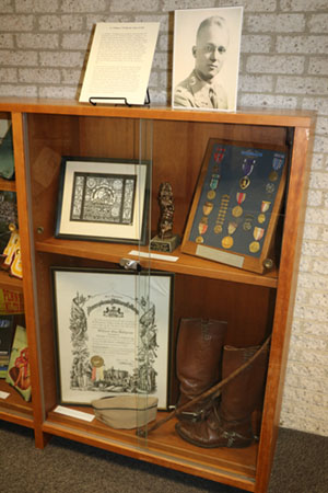 Top Shelf -- Framed Mural, Model of 10th Mountain Division Memorial and Military Medals, including Purple Heart.  Bottom Shelf -- PMC War Diploma, Boots, Riding Crop, and Garrison Cap.
