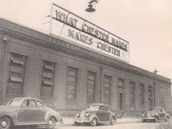 Image of Buidling in Chester with the Sign What Chester Makes Makes Chester on the top and three cars parked in front