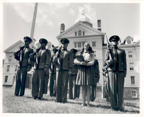 Image featuring 5 cadets in PMC uniforms and one female student standing in front of Old Main