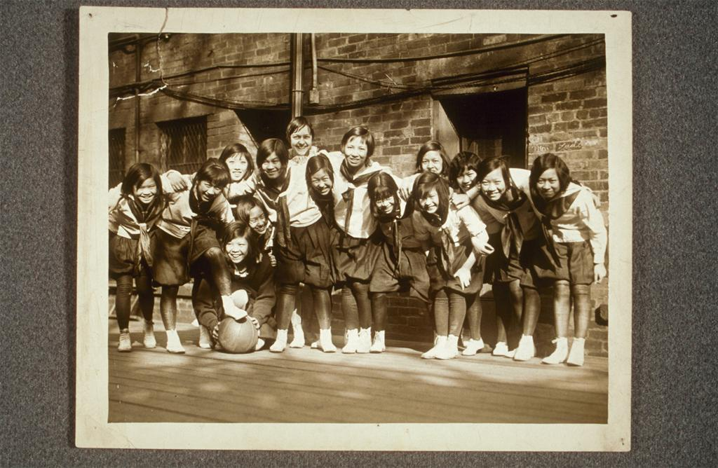 Group photograph of a girls' basketball team, arms linked, one girl in front holding a basketball