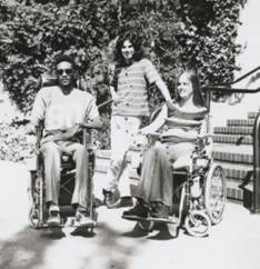 Photograph of two students in wheelchairs and one standing.