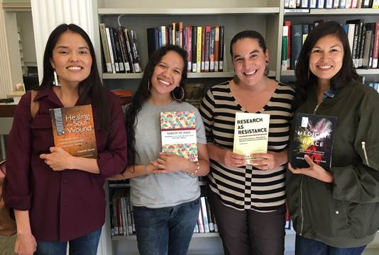 Four women from (RE)generation holding favorite books in front of the Indigenous Social Welfare Collection. Books are Healing the Soul Wound, Guided by the Spirits, Research as Resistance and Medicine of Peace.
