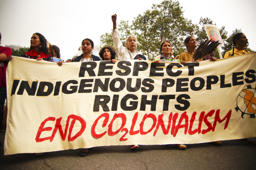 "People holding a banner that says ""Respect Indigenous Peoples Rights: End Colonialism"""