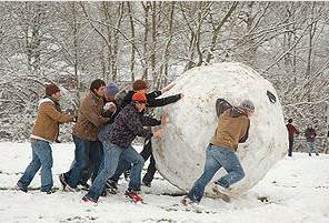 Image of a group of people pushing a huge snowball.