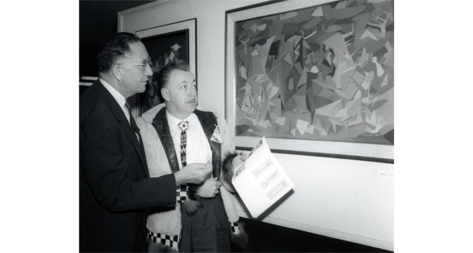 Congressman Ben Reifel and another man admiring a painting by Oscar Howe.