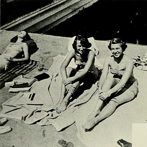 A photo of three people smiling and lounging on the beach