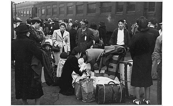 Japanese Americans assembling near trains during relocation