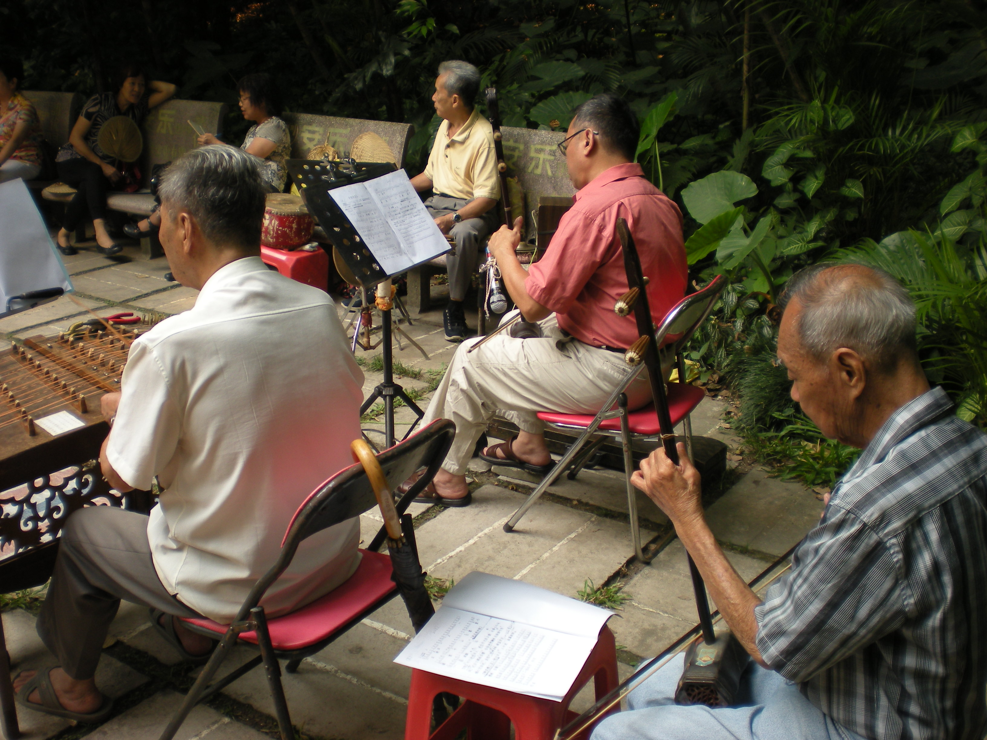 A small group of musicians playing together in a park in Guanzhou, China.