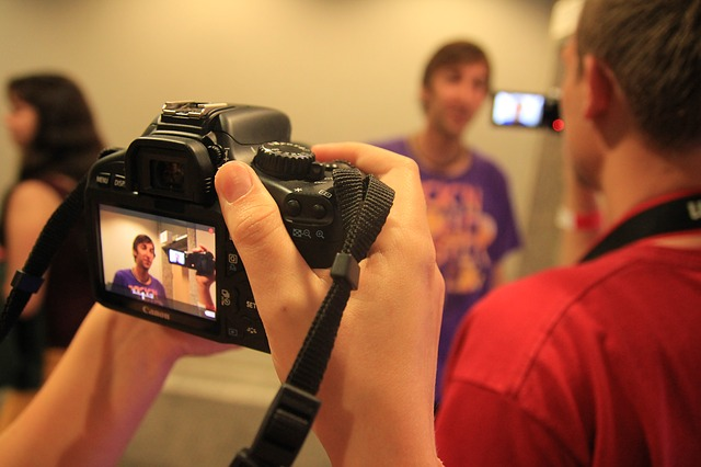 looking through the viewfinder of a camera and recording someone speaking